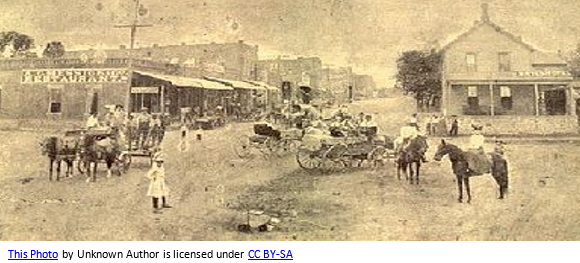 Oklahoma Pioneer by popular US professional genealogy services, Lineages: sepia image of an old town in Oklahoma with people walking on a dirt road, horse drawn wagons, and people riding on horse.
